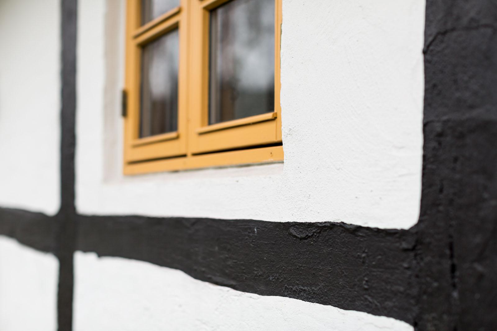 Maling af vinduesrammer og facade på bindingsværkshus tæt på